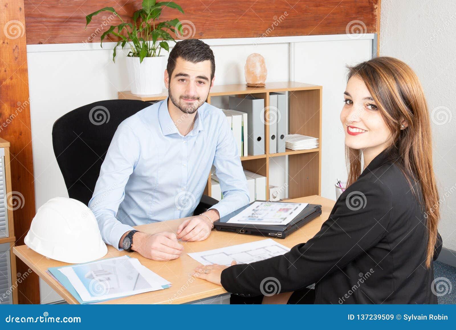 Привлекательные бизнесмены работая в человеке и женщине офиса в деловой встрече