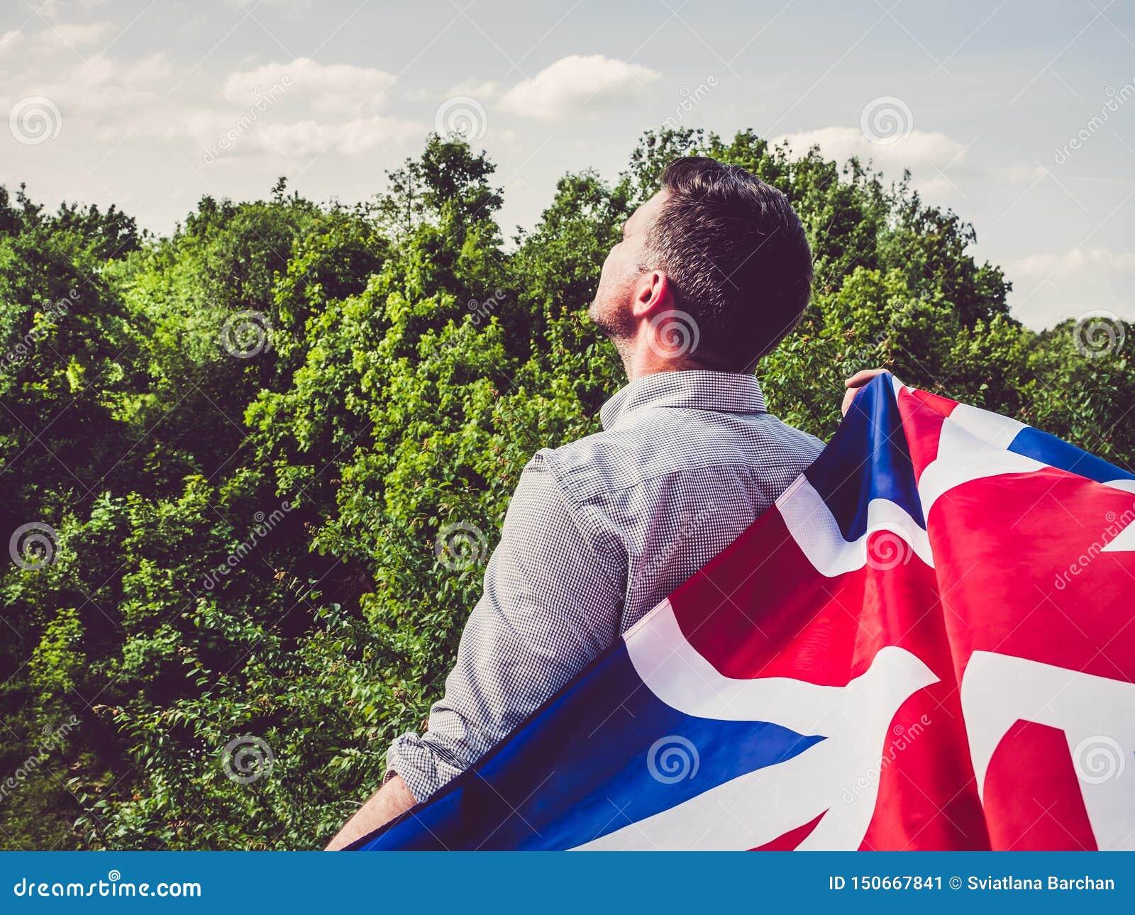 Привлекательный, молодой человек развевая великобританский флаг
