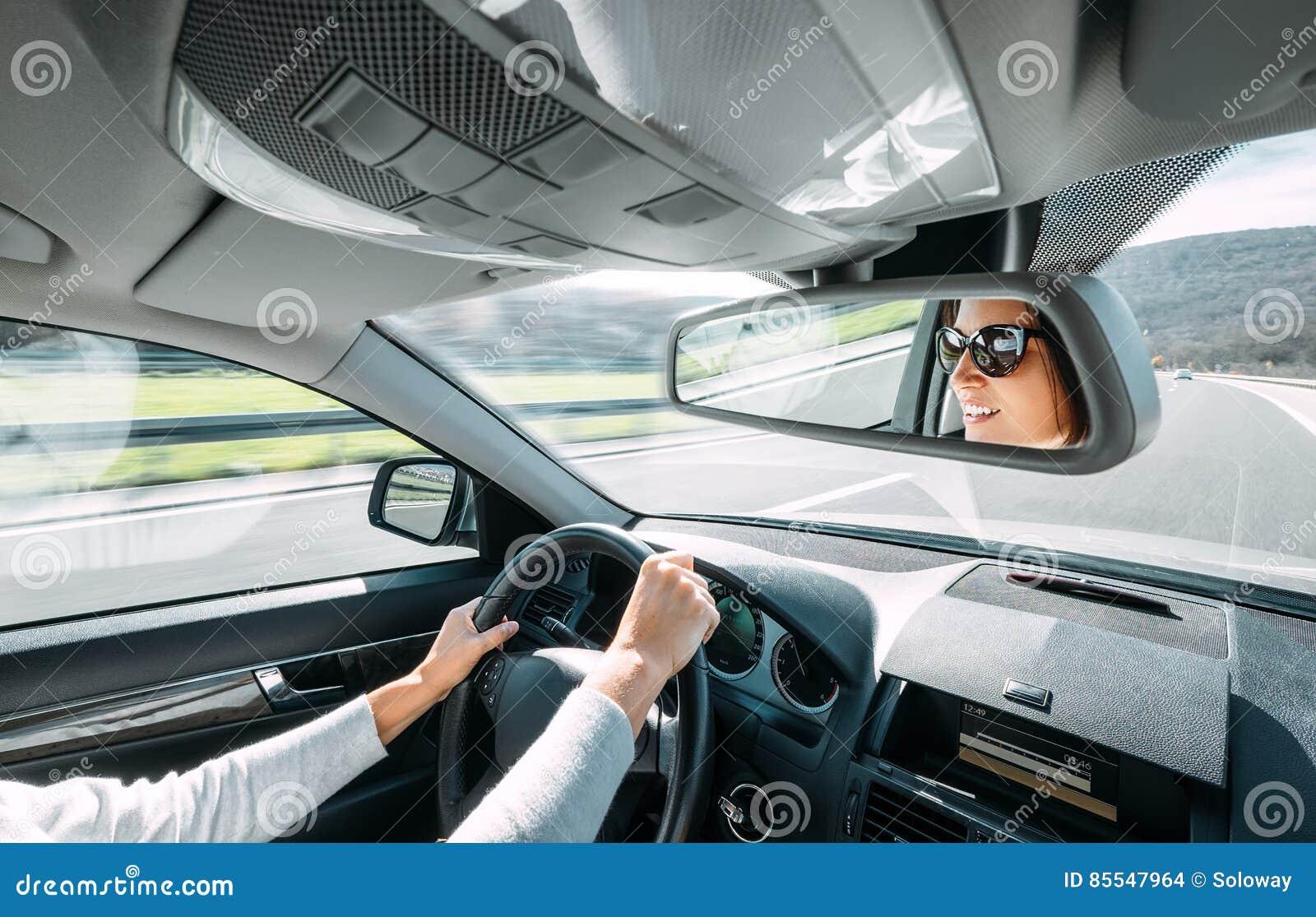 Привод женщины автомобиль отражает в заднем зеркале взгляда