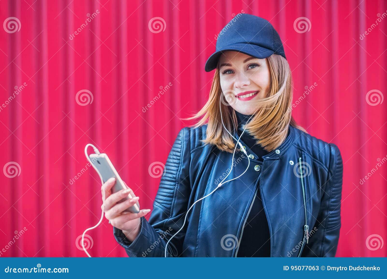 Привлекательная белокурая девушка слушая к музыке на его smartphone