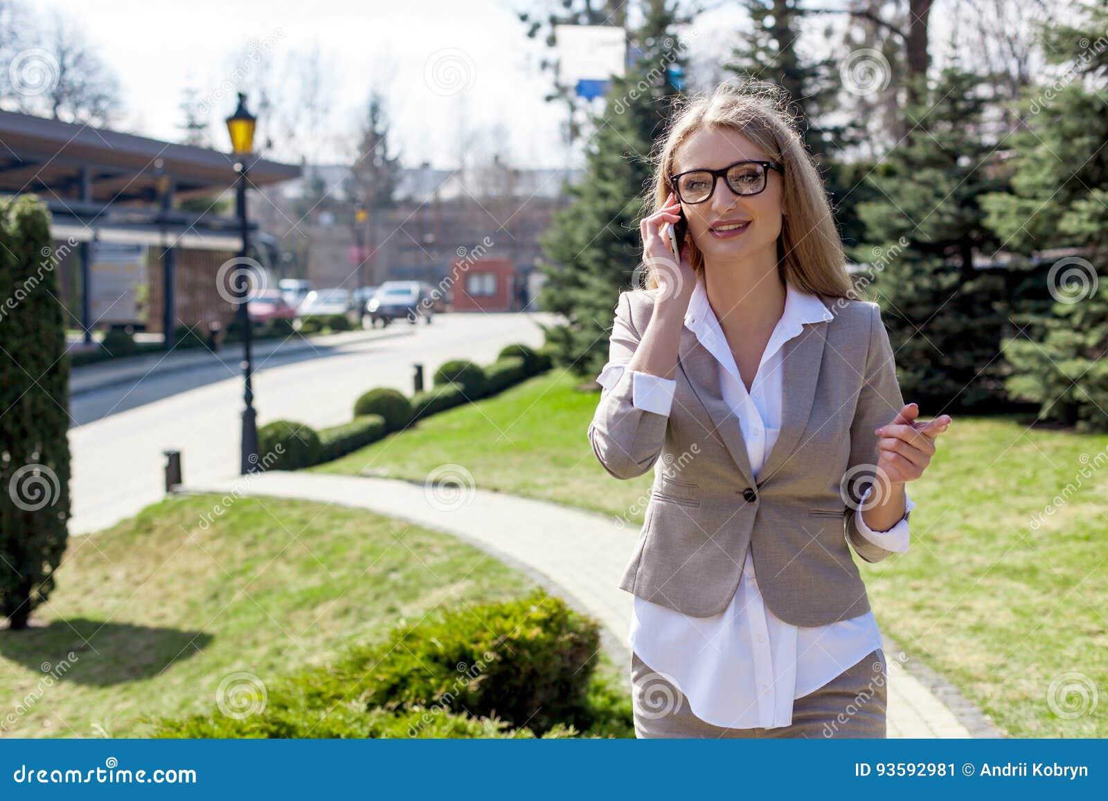Привлекательная молодая коммерсантка говоря на телефоне и усмехаться Костюм и стекла женщины нося