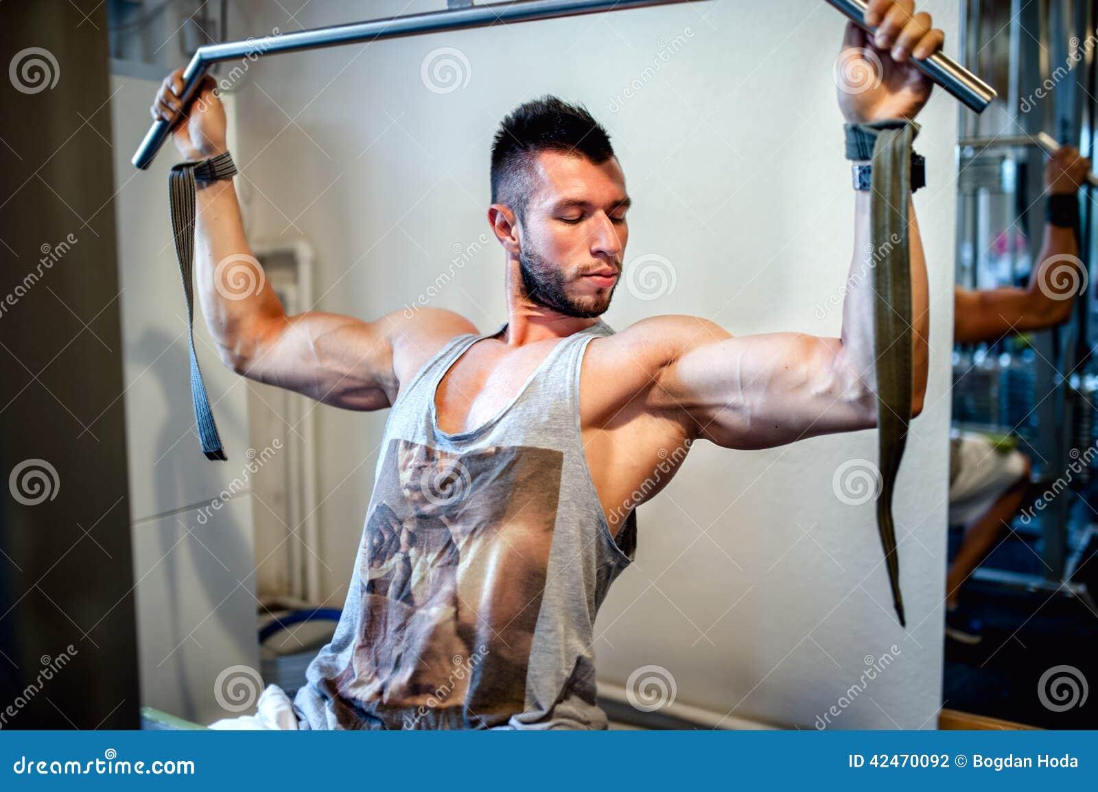 Пригонка, атлетический сексуальный человек разрабатывая в спортзале