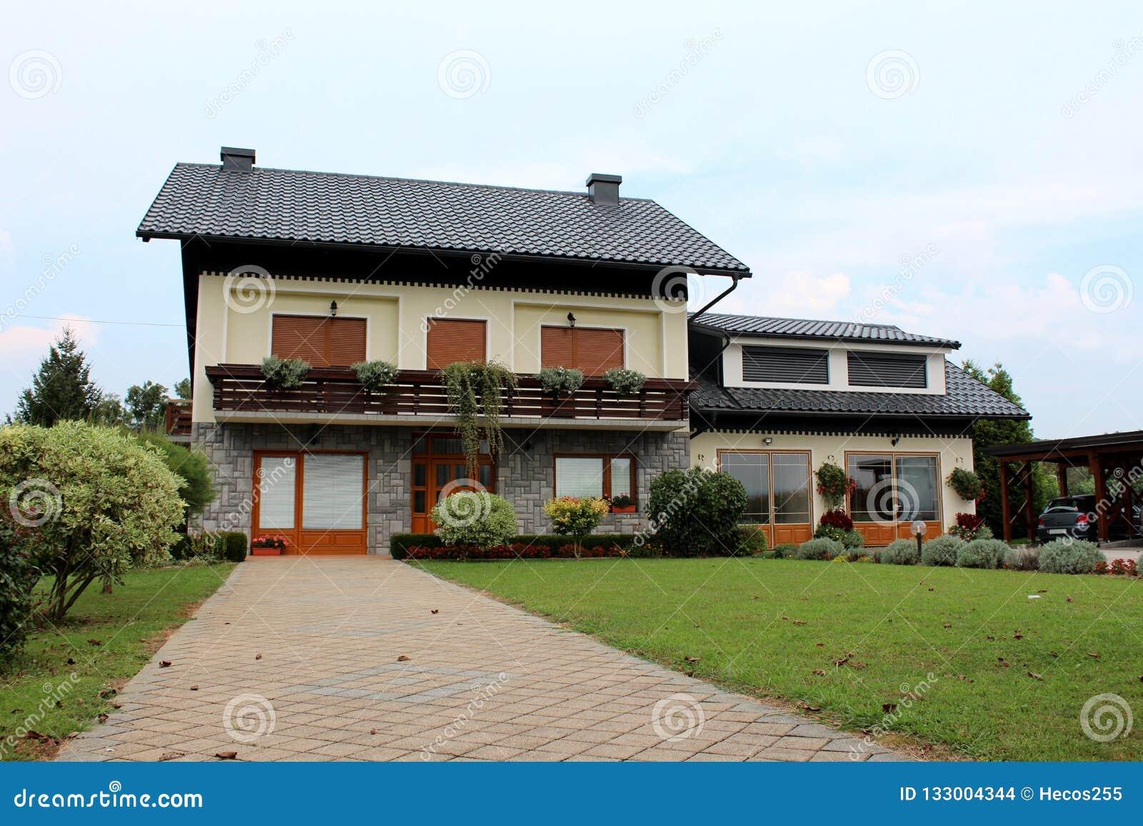 Пригородный дом семьи с каменной подъездной дорогой плиток и новым гаражом окруженными со свежо отрезанной зеленой травой и небол