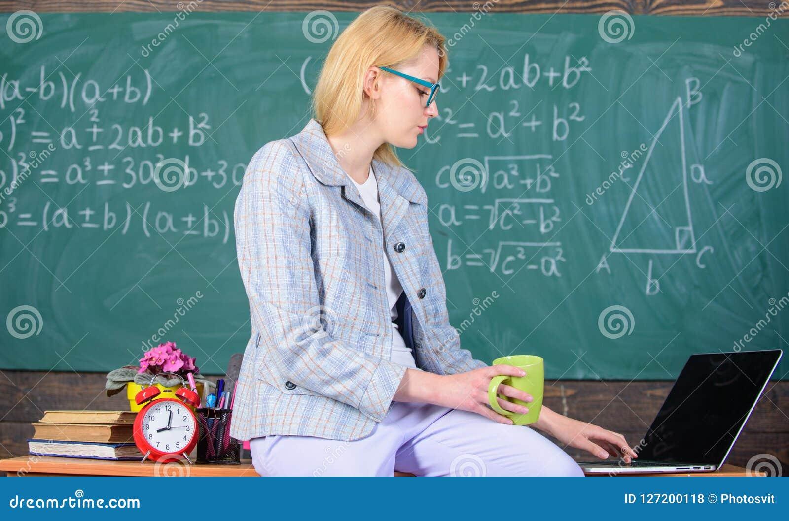 Примите мельчайший пролом Учитель женщины спокойный держит питье кружки сидит предпосылка доски класса таблицы Условия труда