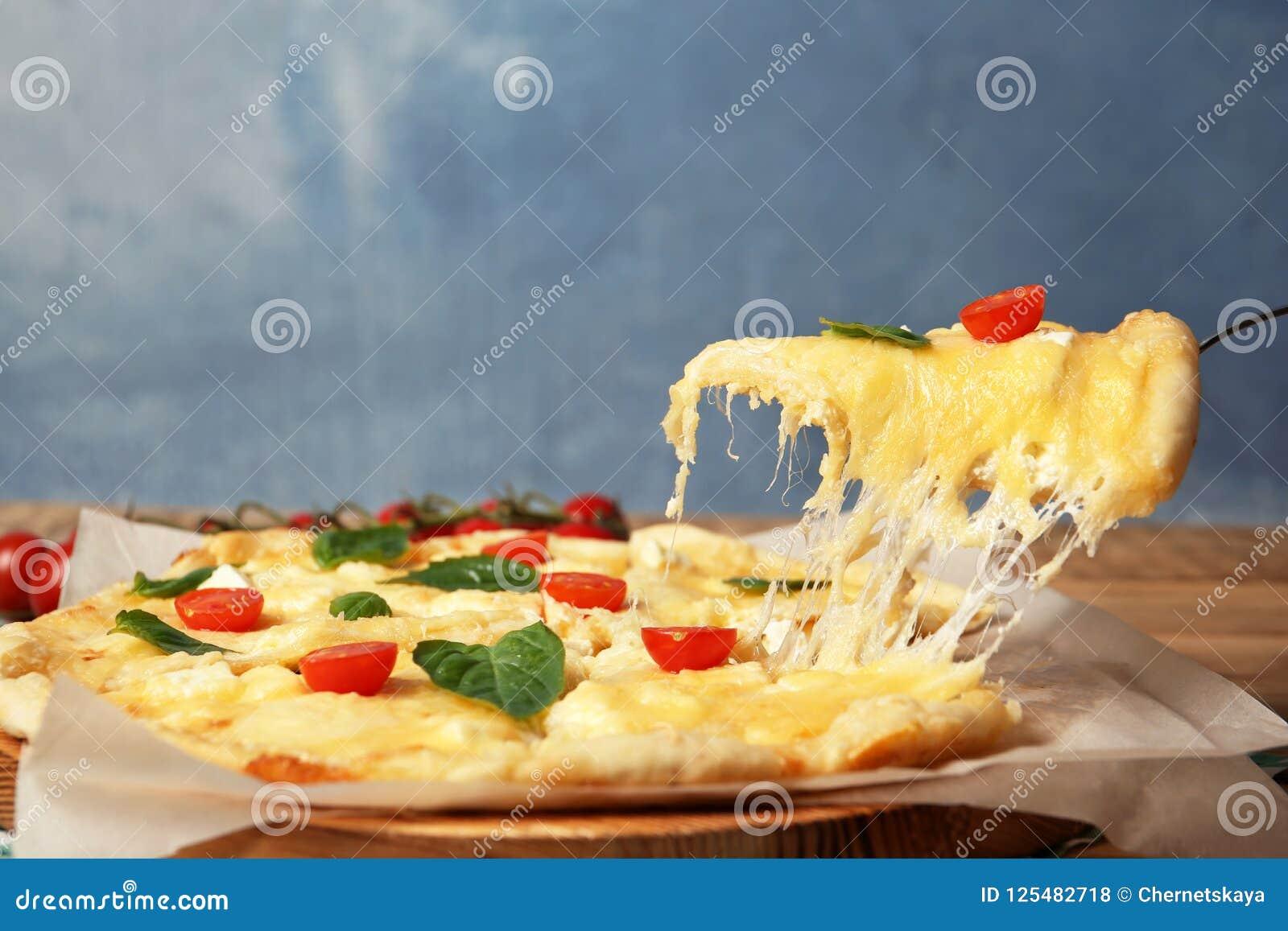 Принимать вкусный домодельный кусок пиццы с расплавленным сыром