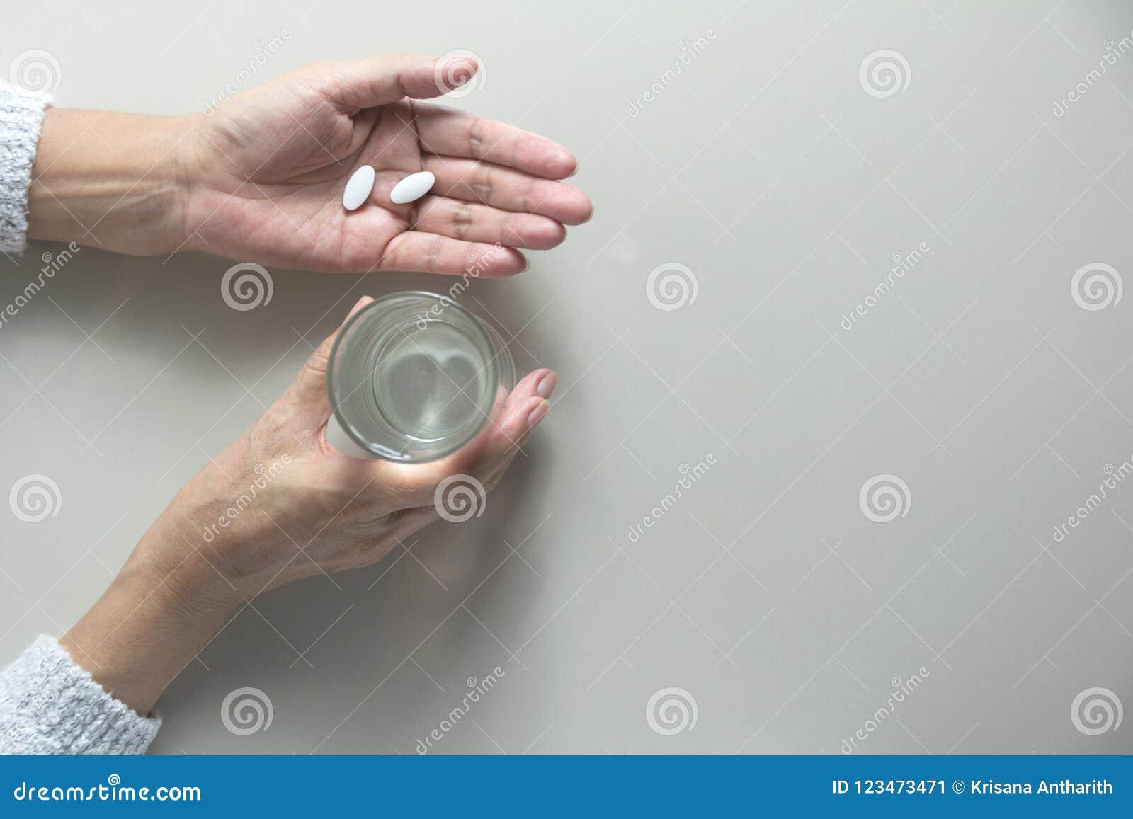 принимать пилек микстуры Женщина держит в руках пилюльки a медицины