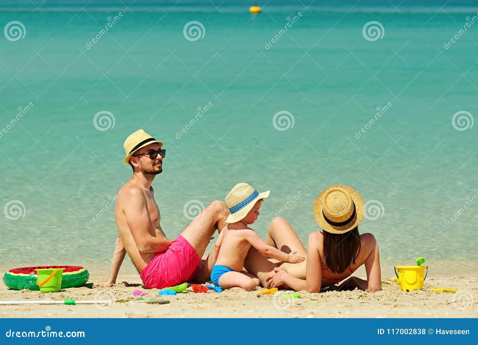 пристаньте семью к берегу Малыш играя с матерью и отцом