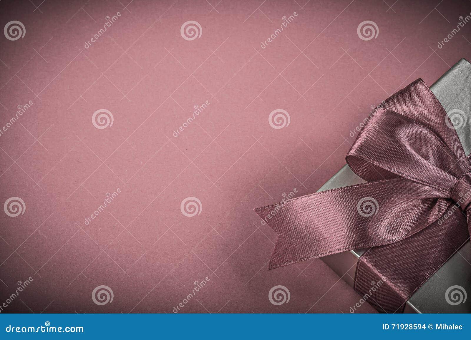 Присутствующая коробка с связанной лентой на красной концепции праздников предпосылки