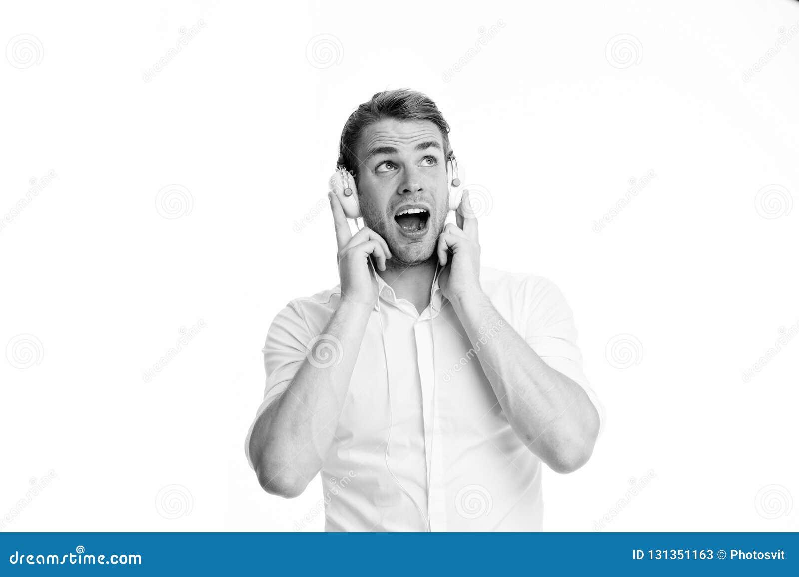 Приятная мелодия Укомплектуйте личным составом слушая любимую песню в наушниках и петь Гай с наушниками слушает музыка Удовлетвор