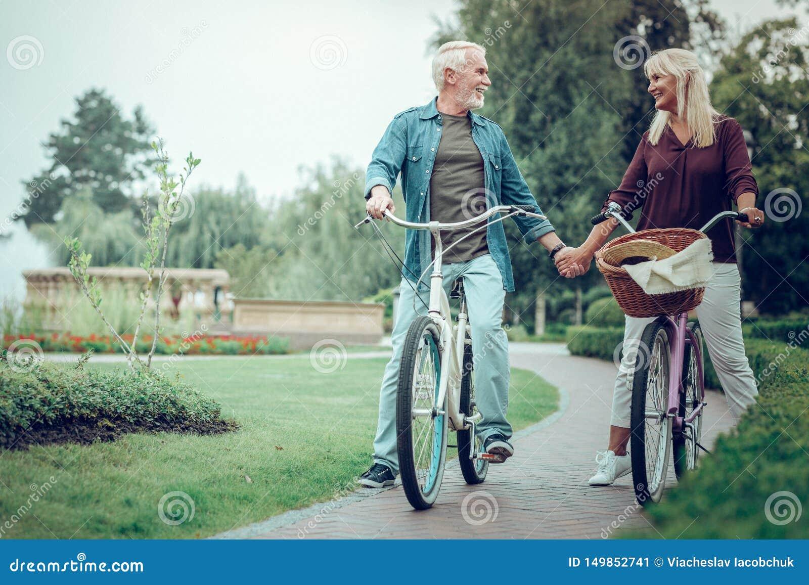 Приятные достигшие возраста пары держа их руки совместно