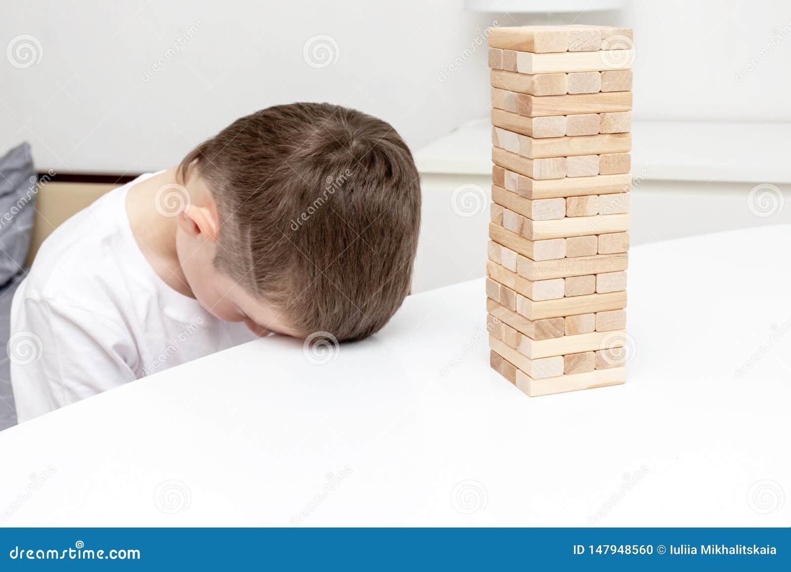 Пробуренный preteen кавказский мальчик пробуя сыграть деревянную настольную игру башни блока для того чтобы развлечь