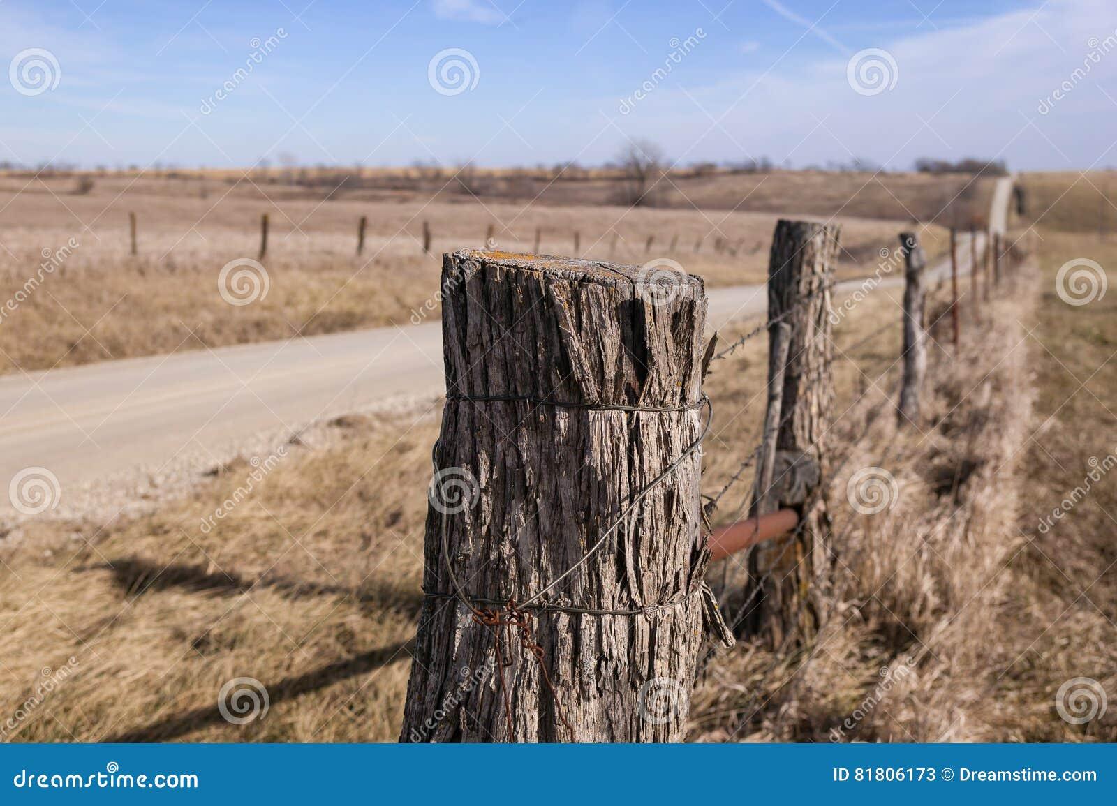 Проволочные изгороди колючки и сельская дорога