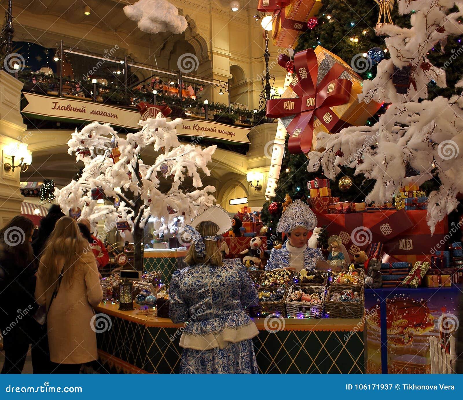 Продавцы в костюмах снега девичьих за счетчиком на ` s Нового Года справедливом в украшенной КАМЕДИ