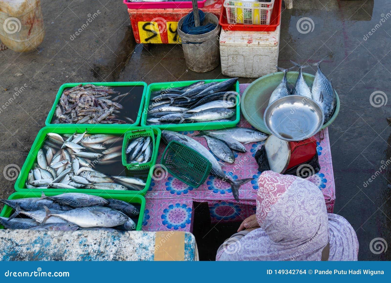 Продавцы рыбы в рыбном базаре Бали jimbaran Он продает различные типы свежих рыб которые как раз caughta мусульманская женщина