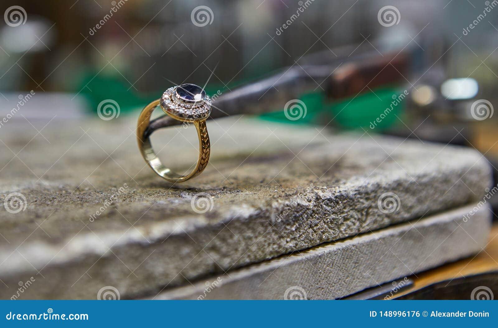 Продукция ювелирных изделий Ювелир делает кольцо золота