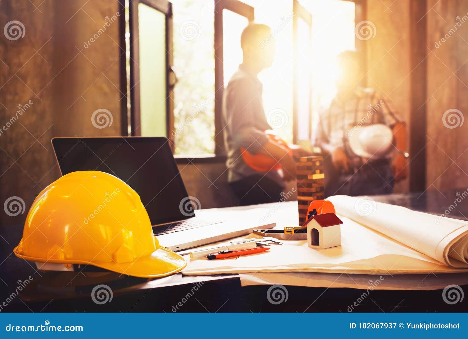 Проектируйте стол с объектом и бумагу с расплывчатым teamwor инженера