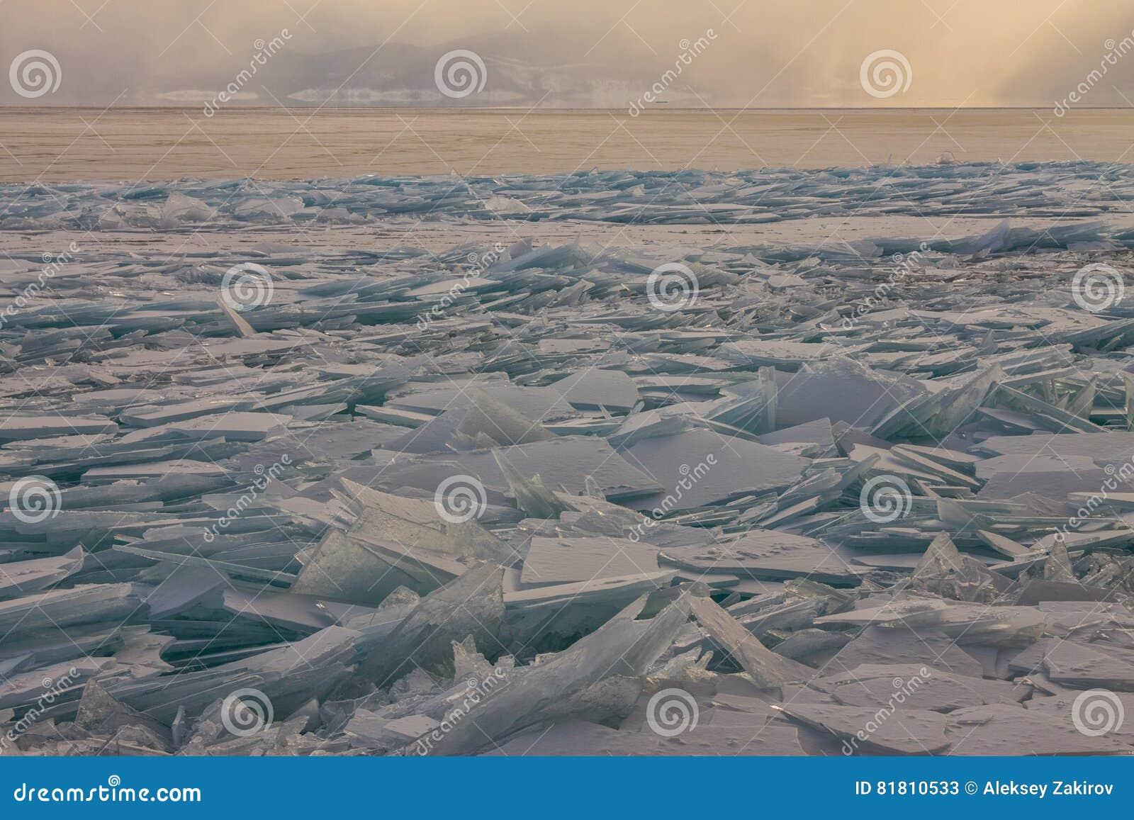 Прозрачные торошения льда Байкала на заходе солнца в тумане