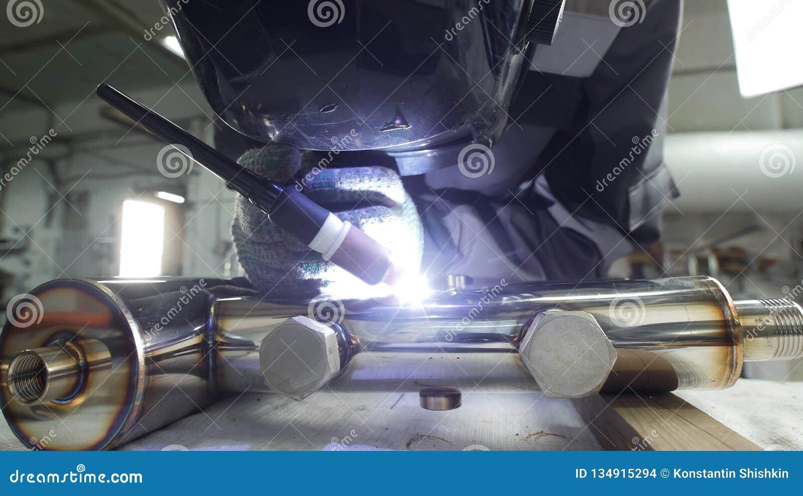 промышленное изготавливание Человек работая с деталью трубы утюга Сваривать