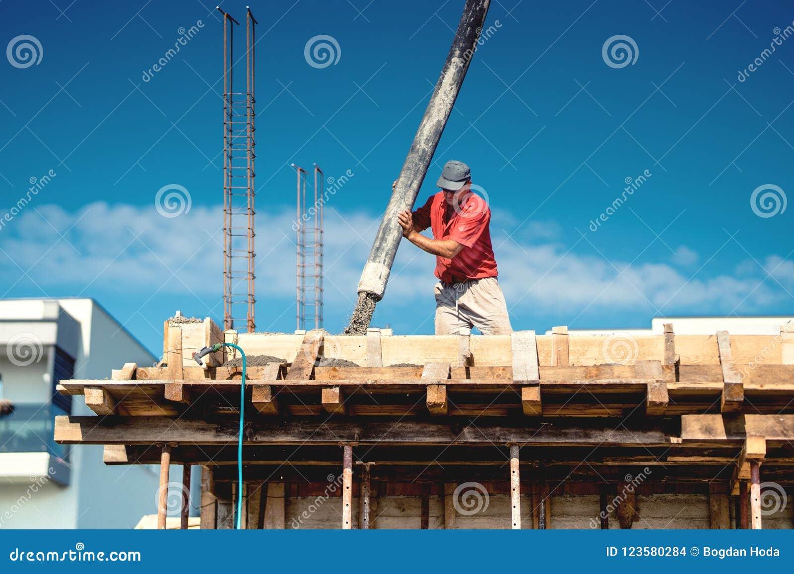 Промышленный работник кладя бетон с автоматическим насосом трубки Рабочий класс на месте с деятельностями при миномета и конструк