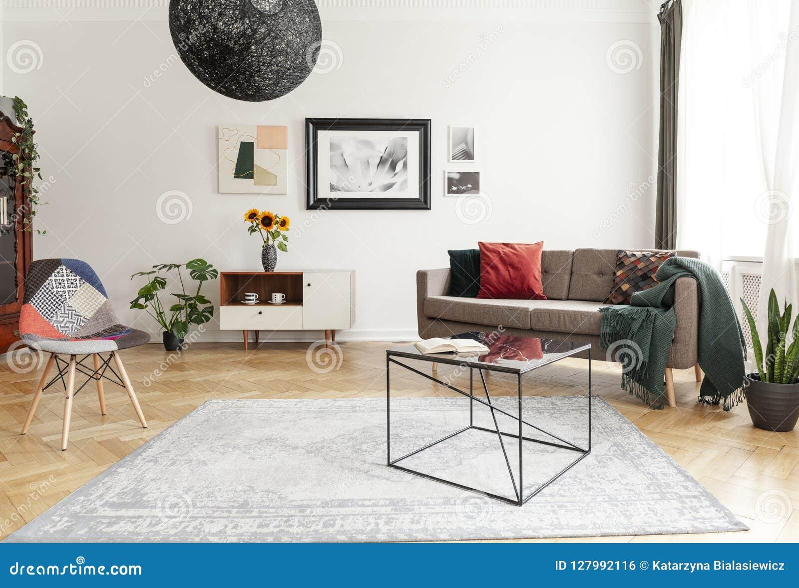 Промышленный черный журнальный стол с мраморной поверхностью и красочный стул заплатки в интерьере живущей комнаты с смешанным ст