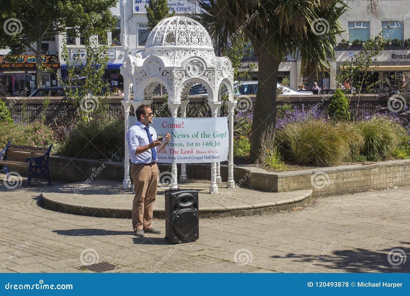 Проповедник улицы Проповедующ хорошие новости спасения через веру самостоятельно в Иисусе Христосе в Sunken садах Бангоре Co вниз