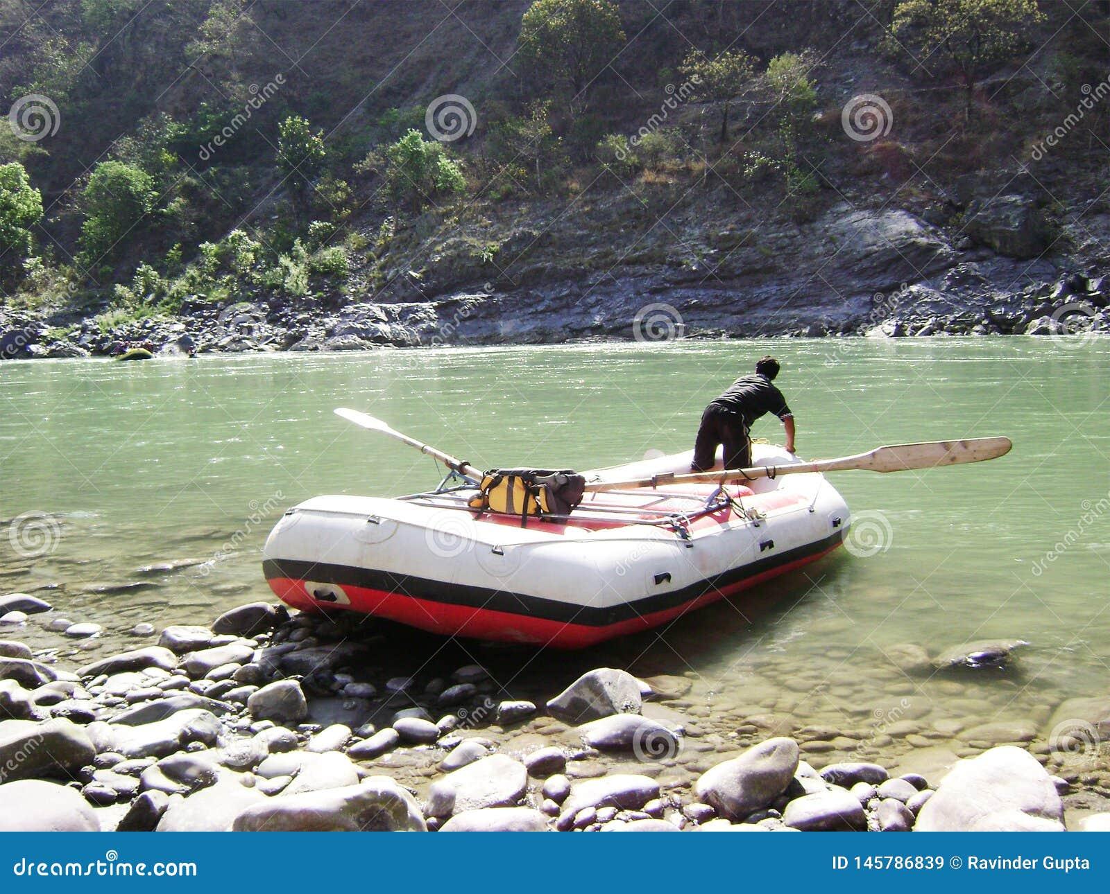Пропуская река, шлюпка с человеком и гора