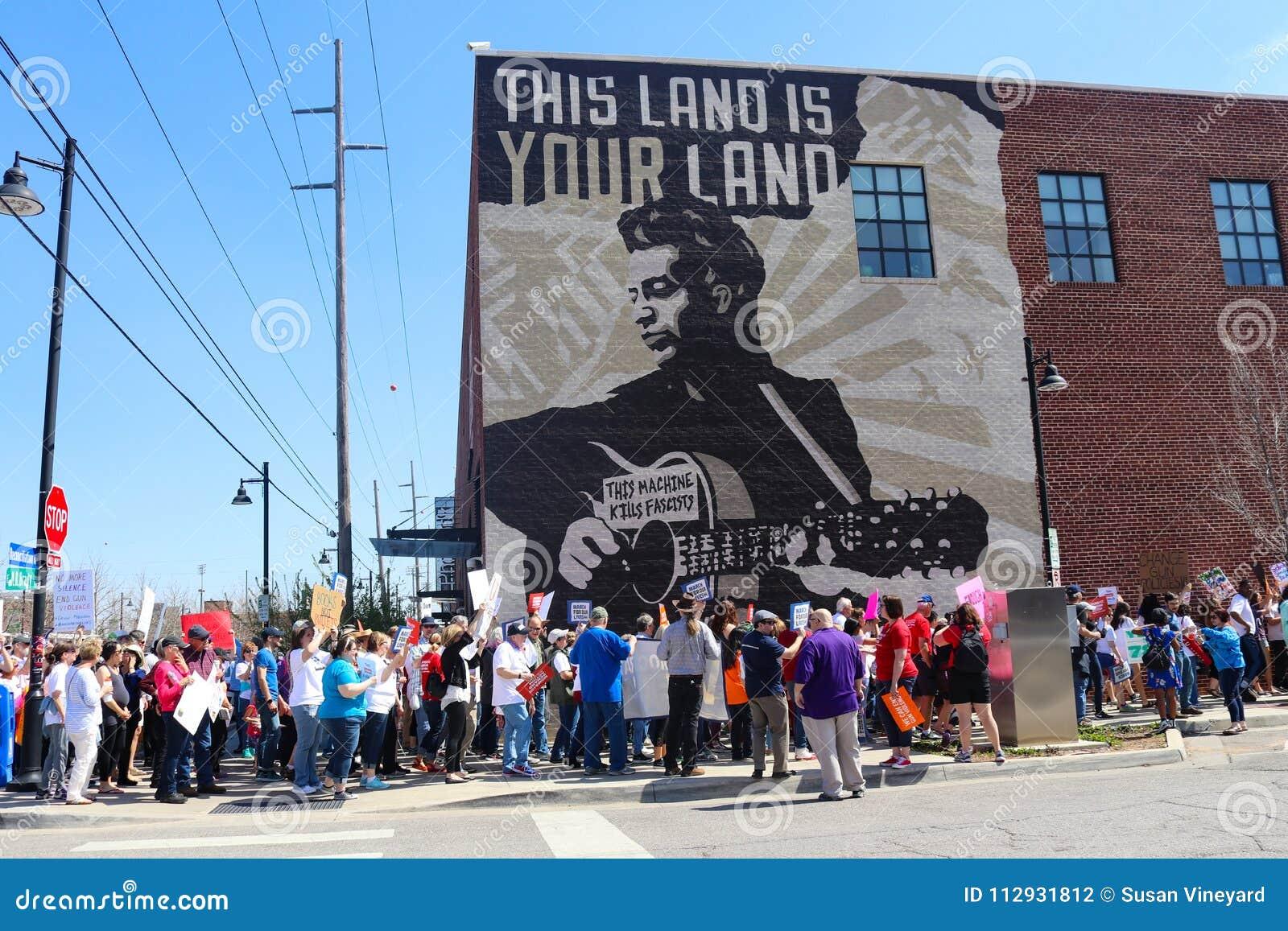 Протестующие маршируют настенной росписью Woody Guthrie которая говорит фашистам убийств этой машины на протесте в марте на всю ж