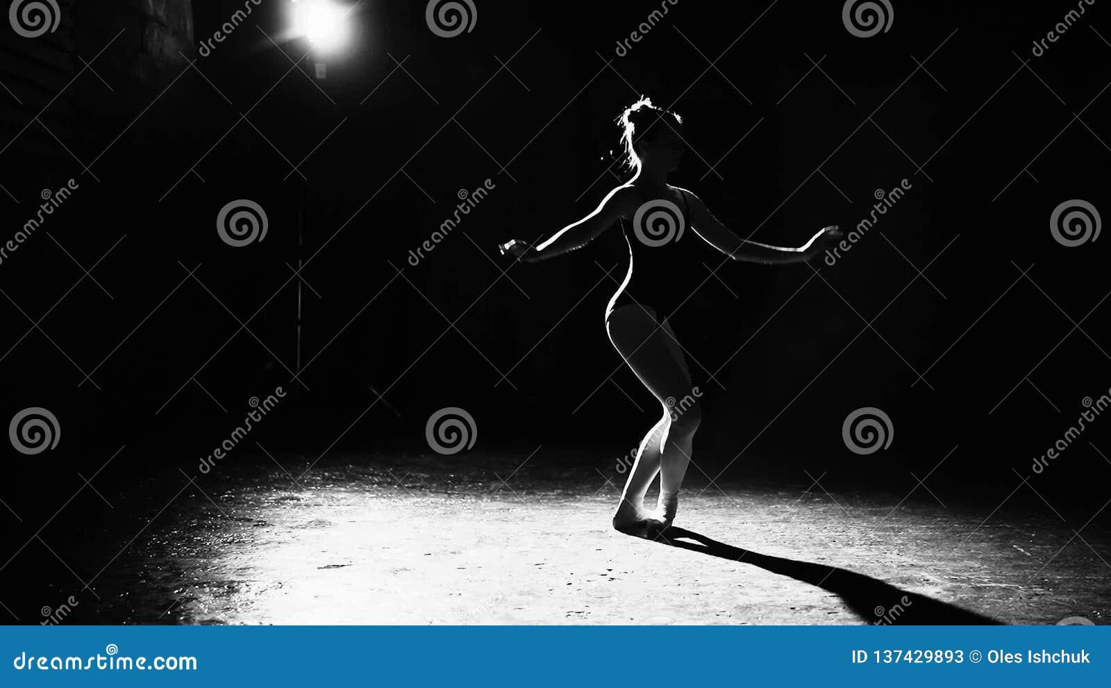 Профессиональные грациозные гибкие танцы балерины на ее ботинках балета pointe в фаре на черной предпосылке в студии сток-видео