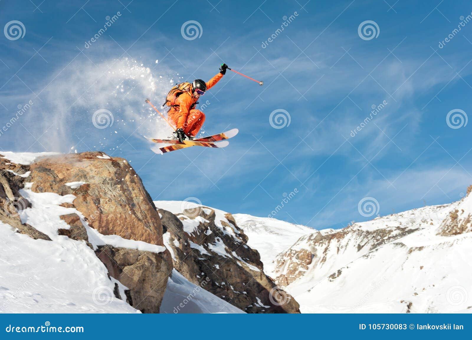 Профессиональный лыжник делает скачк-падение от высокой скалы против голубого неба выходя след порошка снега в