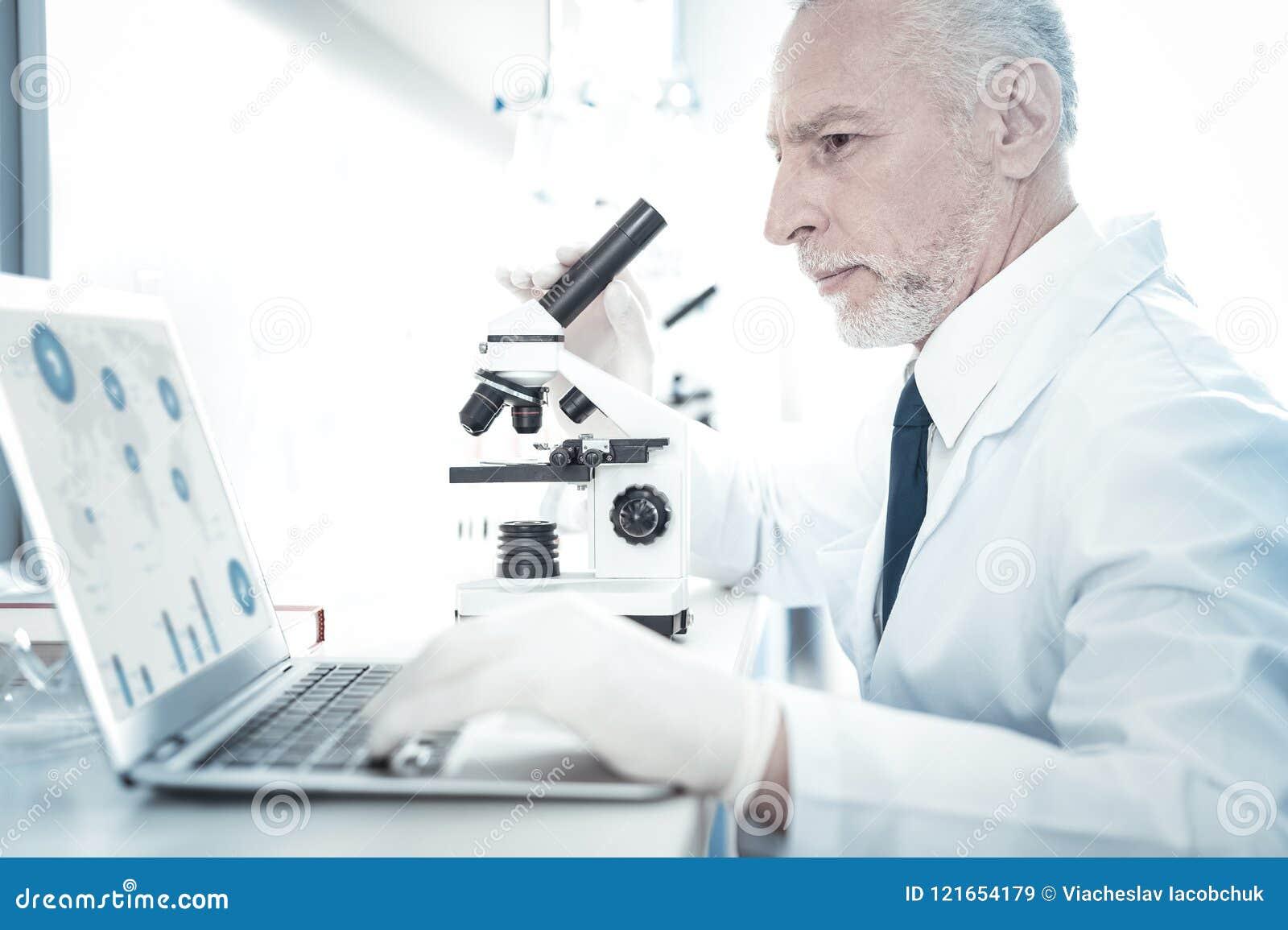 Профессиональный опытный исследователь смотря экран компьтер-книжки