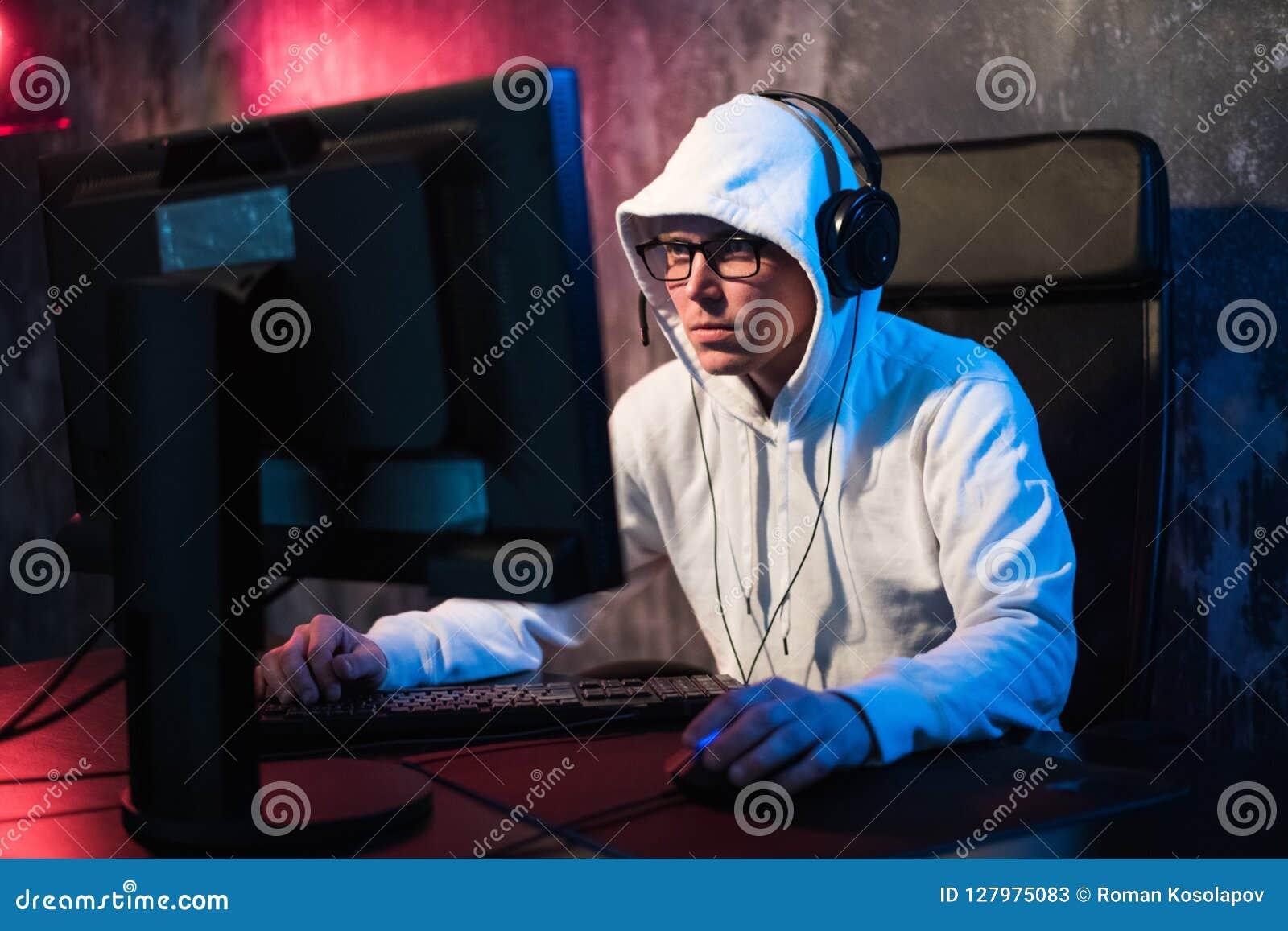 Профессиональный Gamer мальчика играет в видеоигре на турнире eSports или в интернет-кафе Он носит наушники и говорит