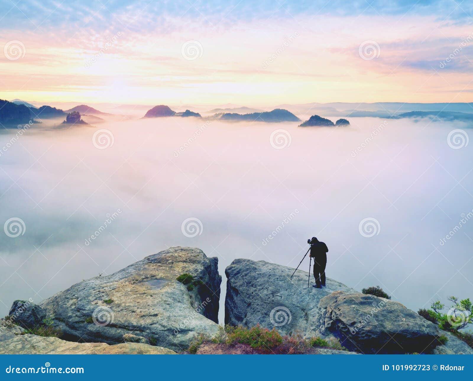 Профессионал на скале Фотограф природы принимает фото с камерой зеркала на пике утеса Мечтательный туман