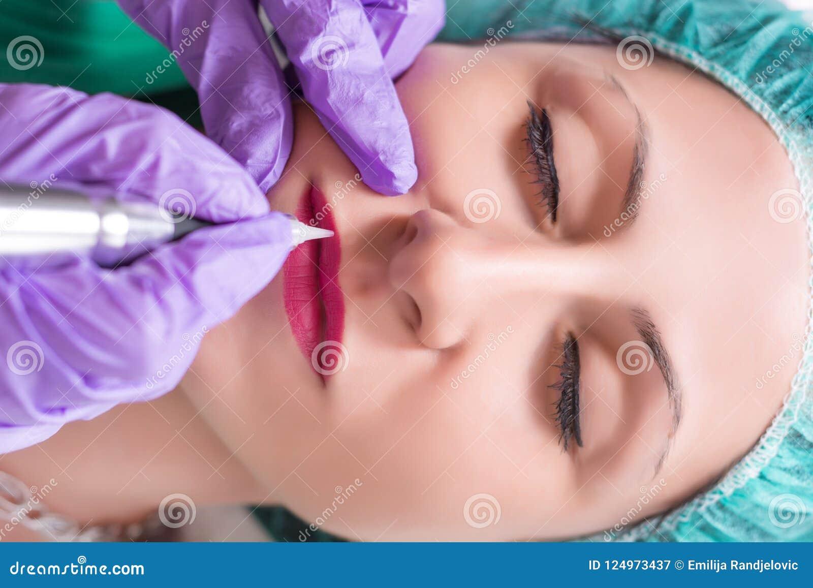 Профессионал прикладывает процедуру постоянного состава на губах женщины