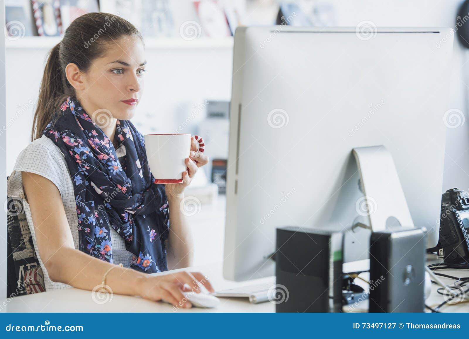 Профессионал женщины использует компьютер выпивая напиток