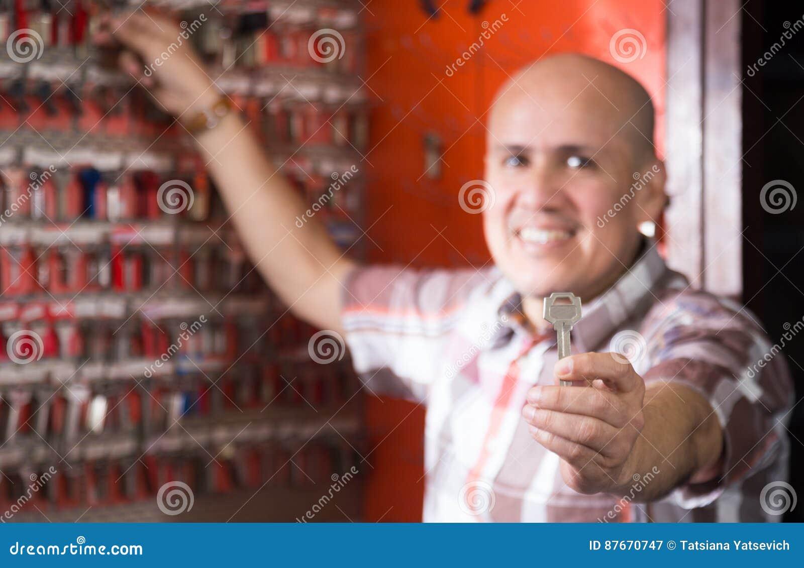 Профессионал предлагая новый ключ на стойке в locksmith