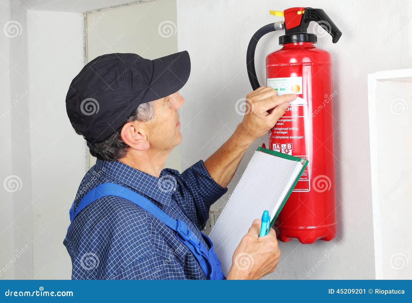 Профессионал проверяя охваченный огнем гаситель