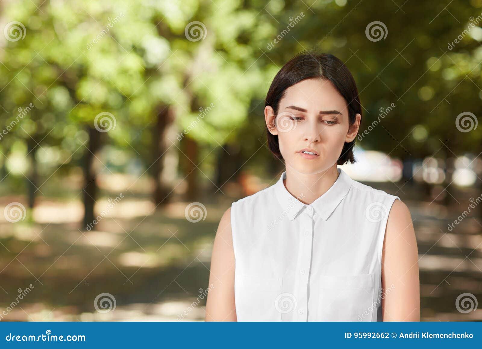 Профессиональная привлекательная женщина в вскользь рубашке на естественной предпосылке Уверенно дама идущ и смотрящ вниз в парке