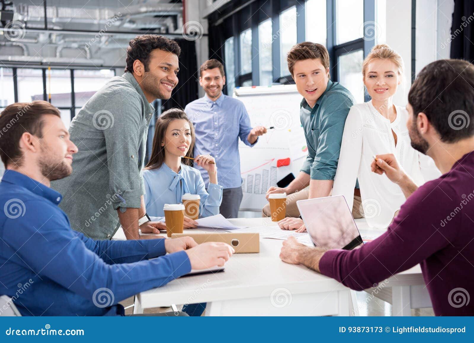 Профессиональные предприниматели обсуждая и коллективно обсуждать совместно на рабочем месте в офисе