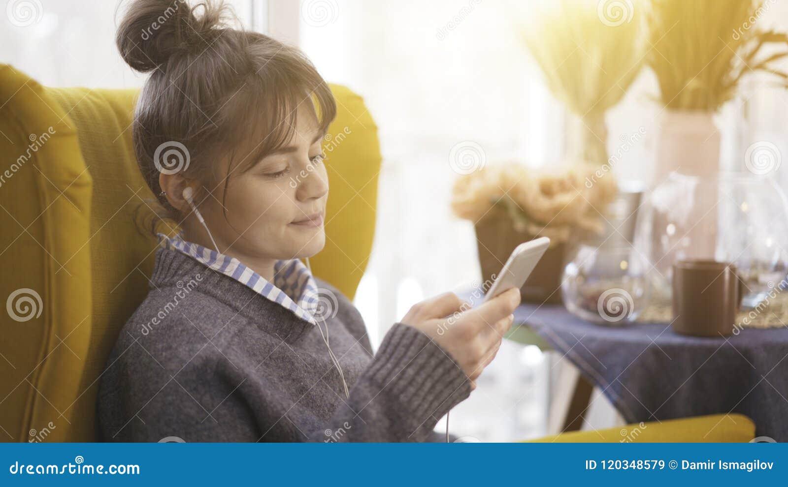 Профиль портрета девушки в наушниках держа телефон