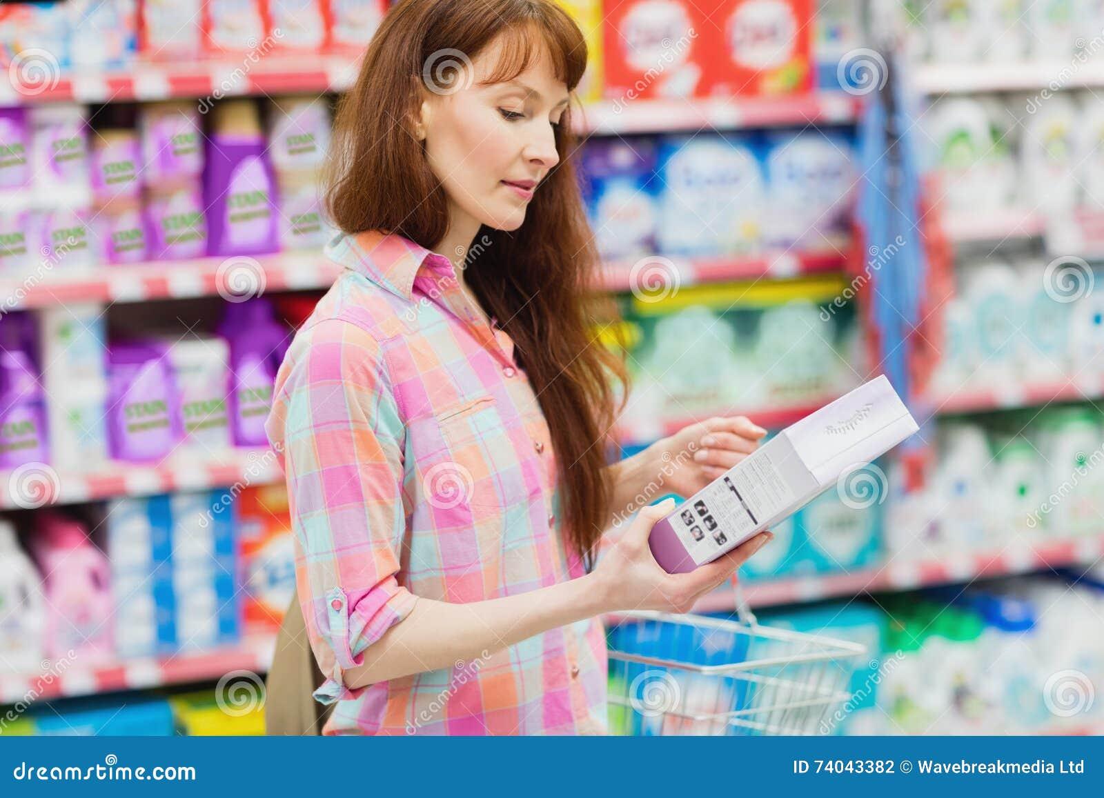 Профилируйте взгляд женщины при корзина для товаров держа продукт