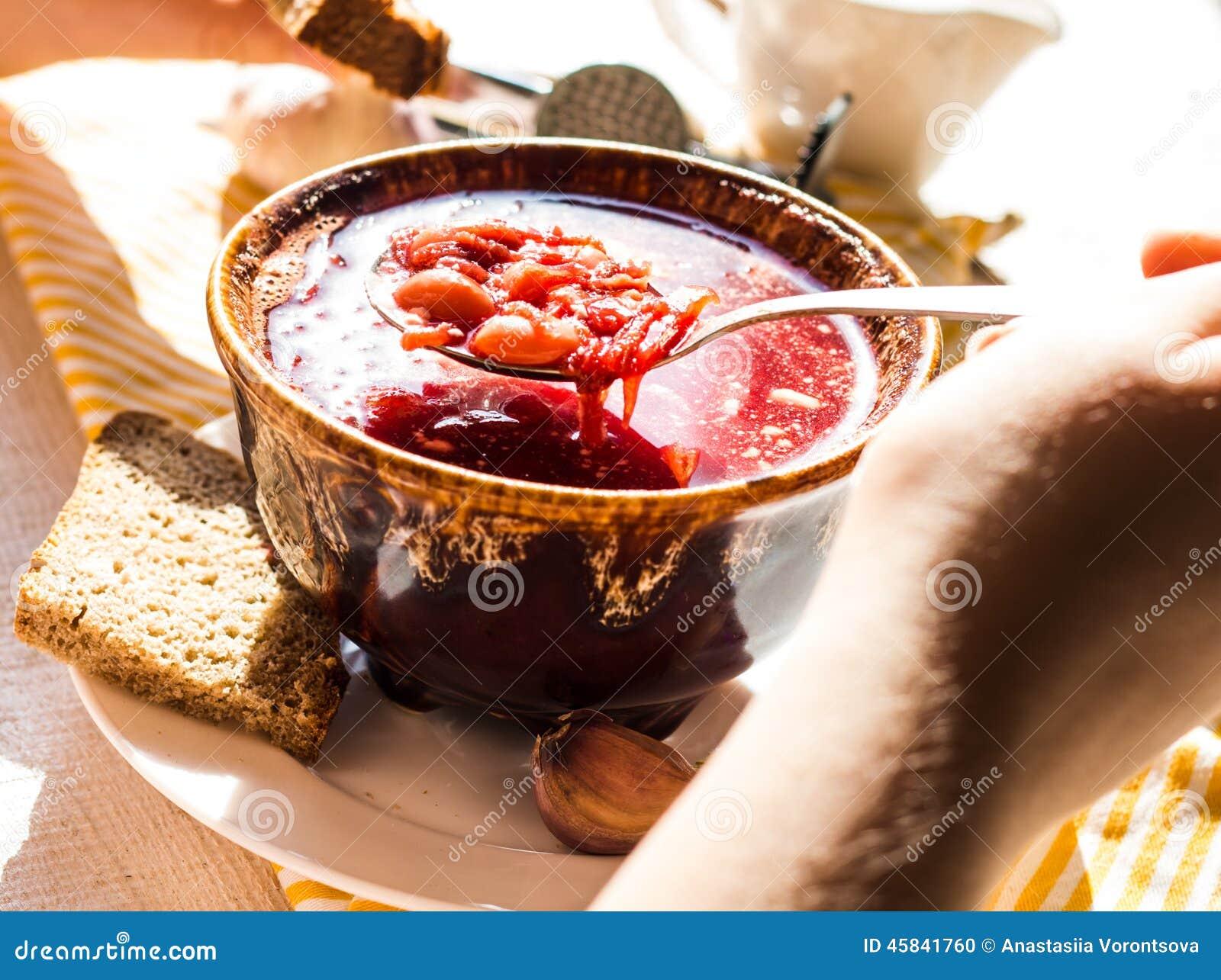 Процесс еды красного борща с сметаной, рукой, гончарней