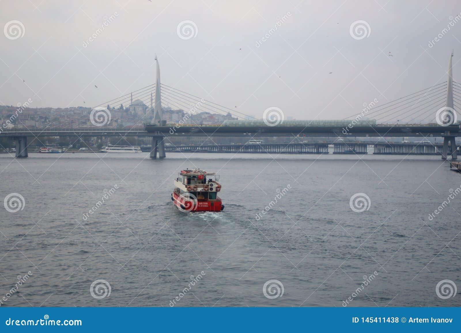 Прочная красная шлюпка плавая к золотому мосту метро рожка