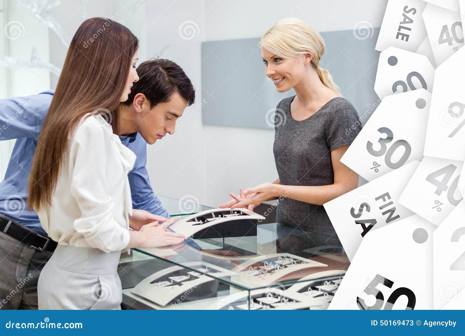 Продавец помогает парам для того чтобы выбрать ювелирные изделия на продаже