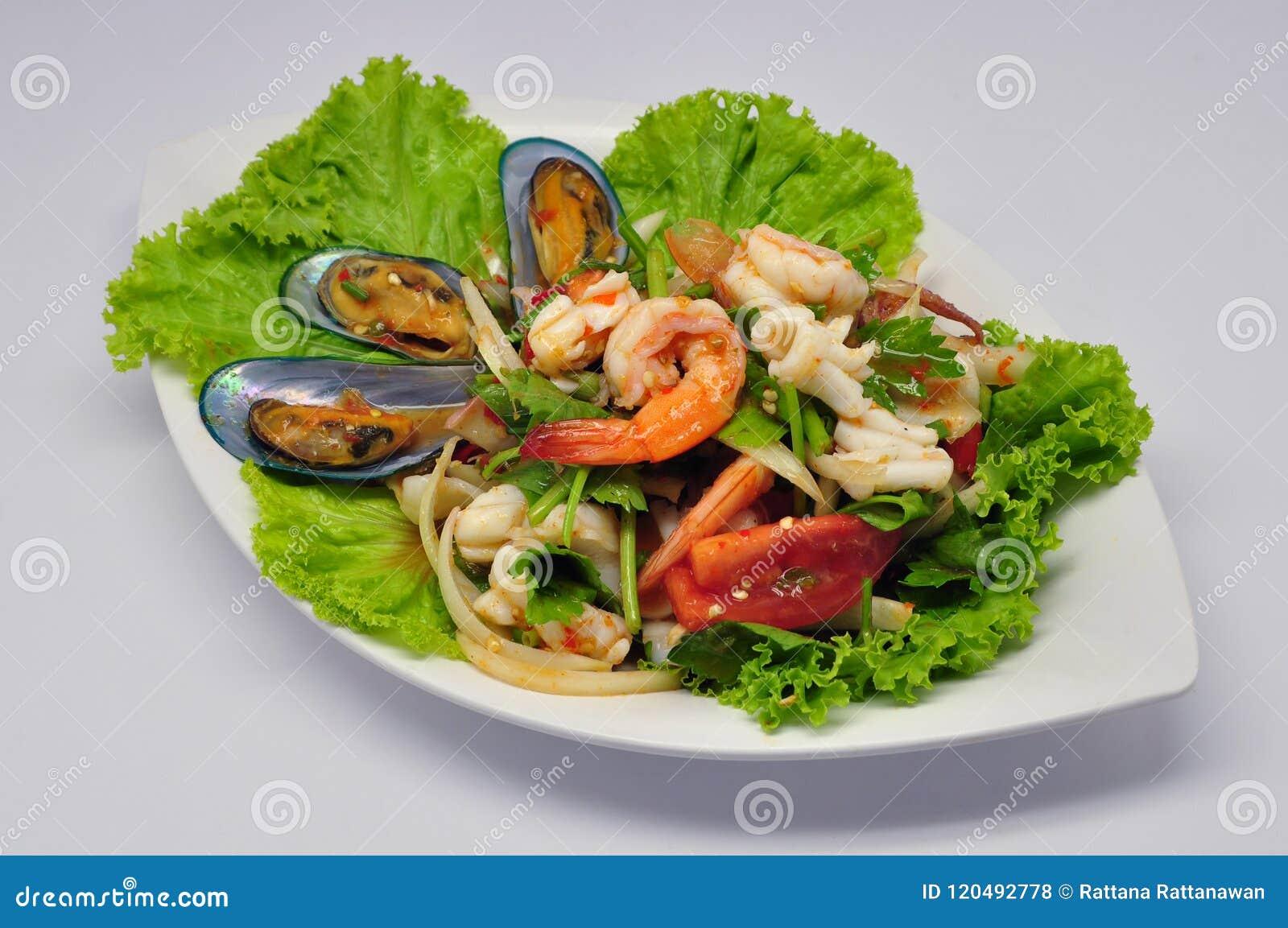 Пряный смешанный салат Yum Talay морепродуктов на белой плите