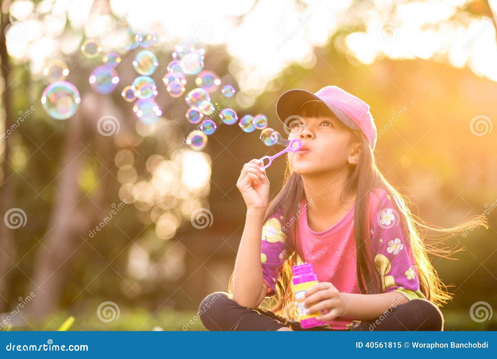 Пузыри мыла маленькой азиатской девушки дуя