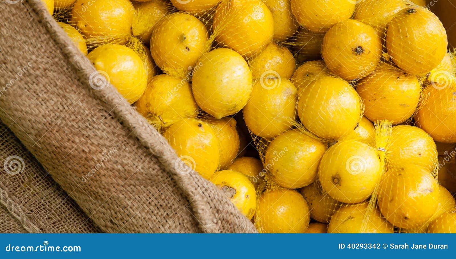 Пуки положенных в мешки лимонов в дисплее мешковины