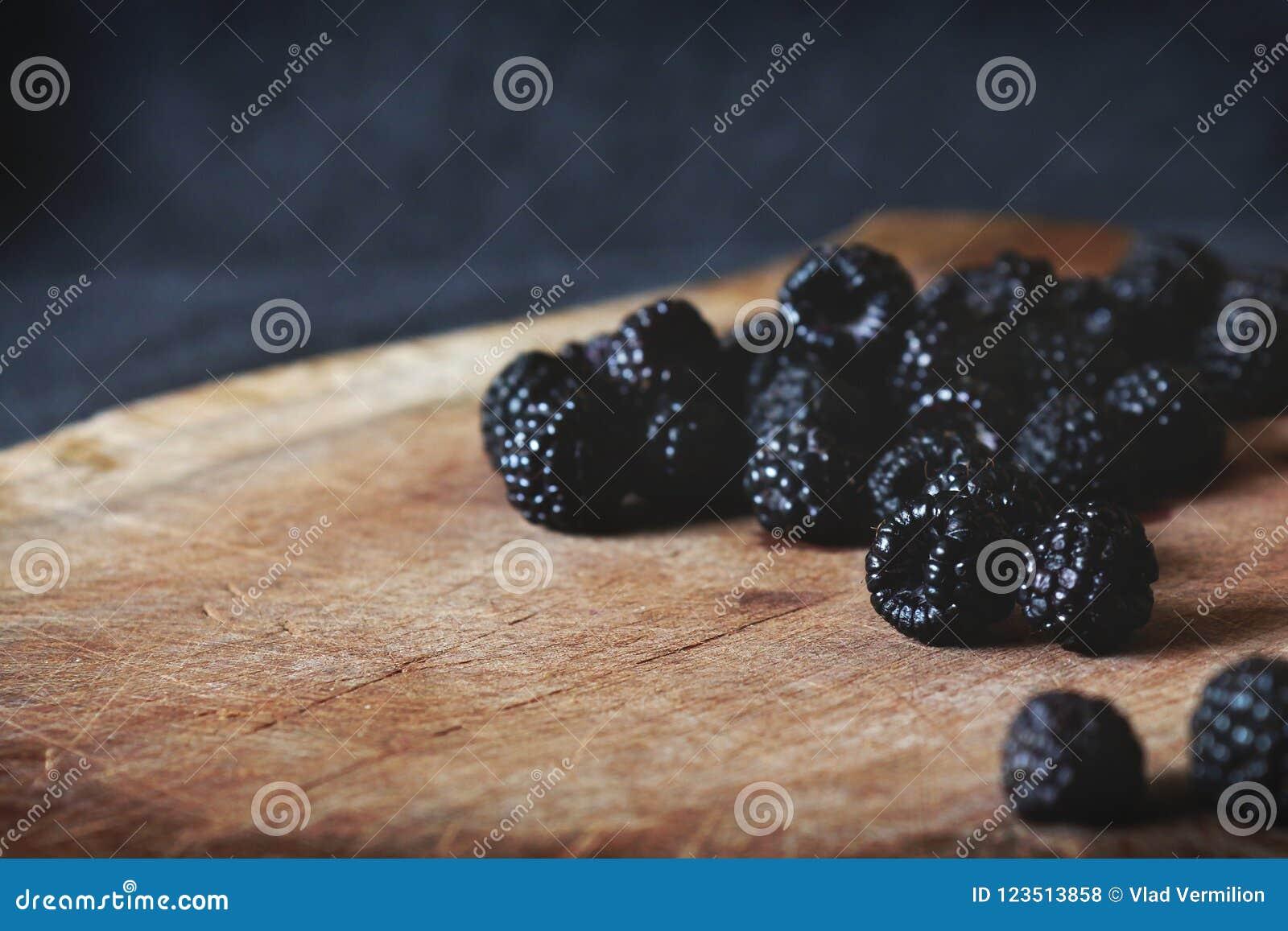Пук ежевик на разделочной доске с черной предпосылкой позади