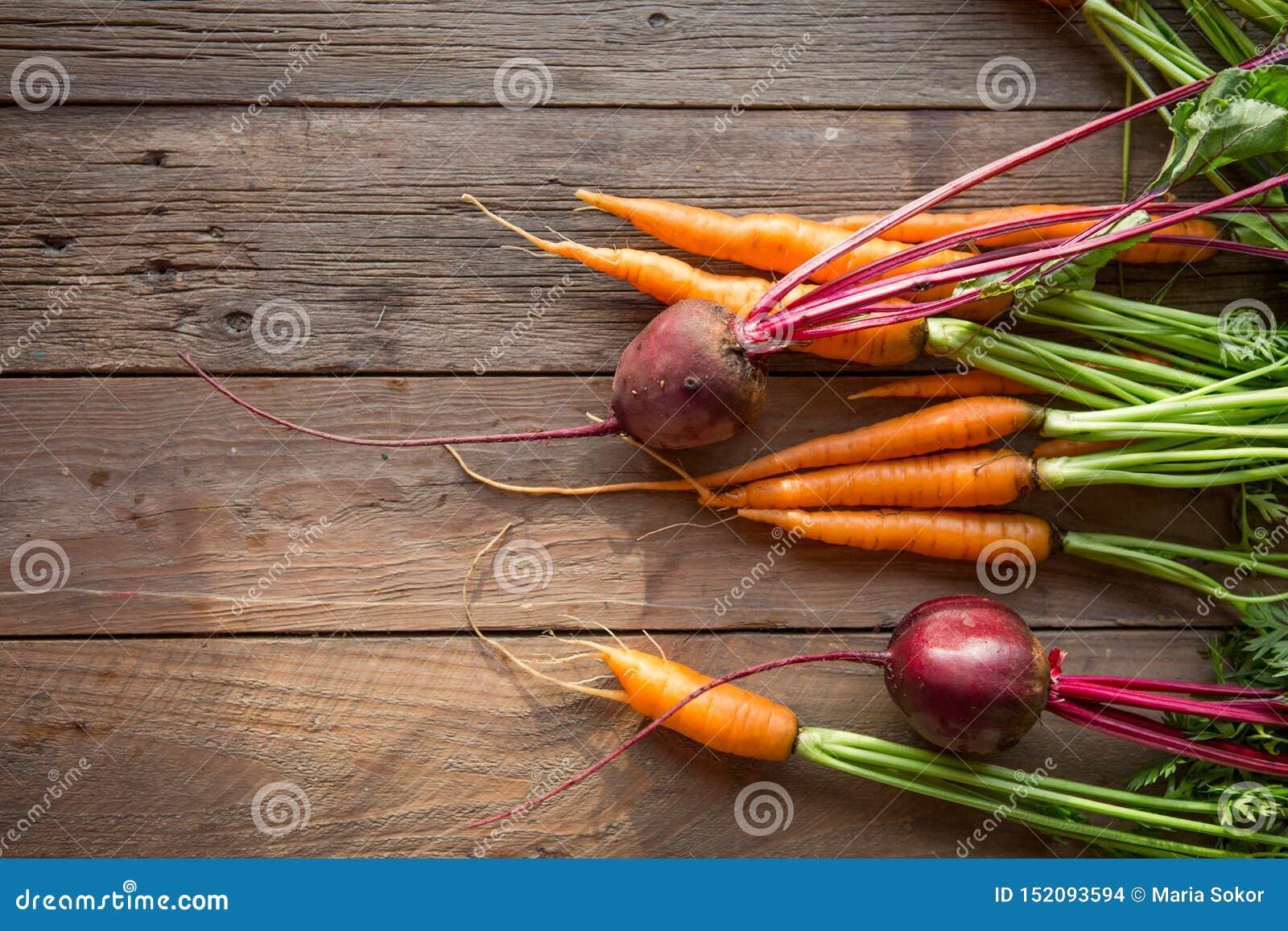 Пук морковей и бураков Свежие моркови, куча бураков с зелеными стержнями Сырцовые моркови и бураки на деревенской деревянной задн