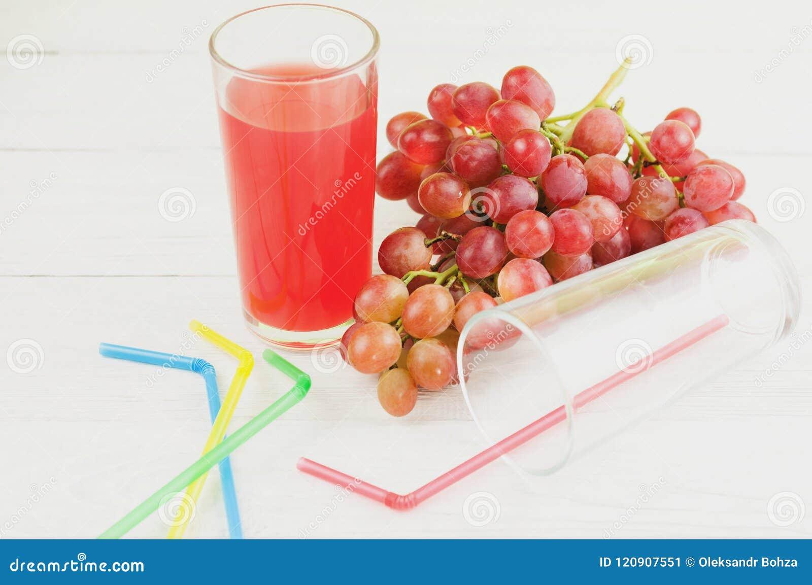 Пук свежих зрелых розовых виноградин приближает к прозрачное и хрупкое стеклянному вполне сока около пустого стекла с пластичным