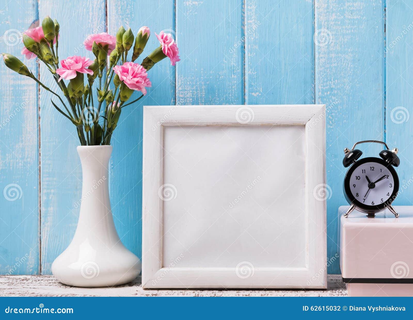 Пустая белая рамка, розовые цветки и будильник